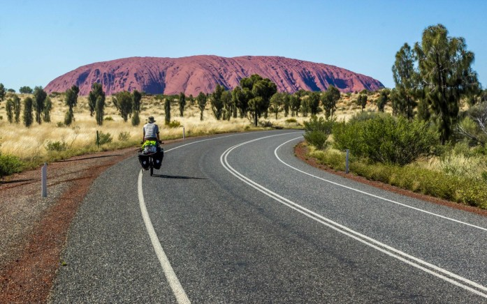 A bike touring cyclist with panniers rides to Uluru in Outback Australia