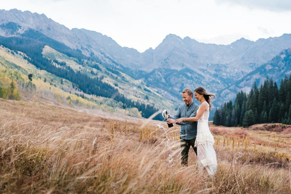 Couple pops champagne by Colorado mountain range