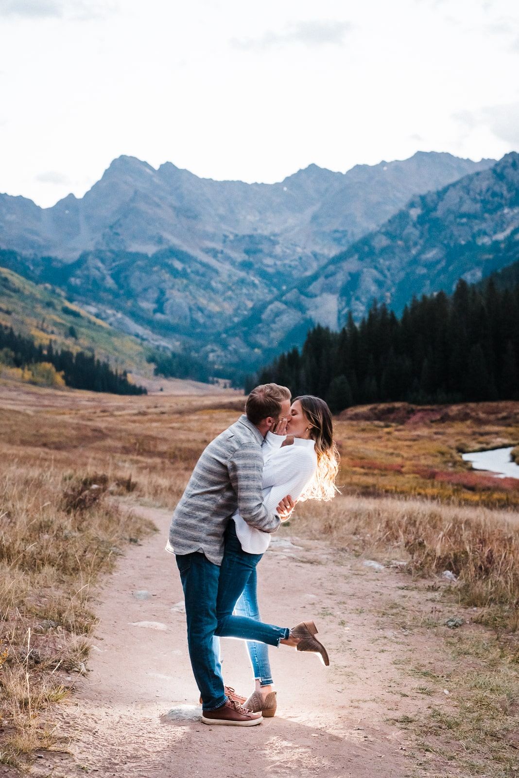 Couple kisses in front of the Rocky Mountains at Piney River Ranch in Colorado. Piney River Ranch is one of the best engagement photo locations in Colorado and near Denver.