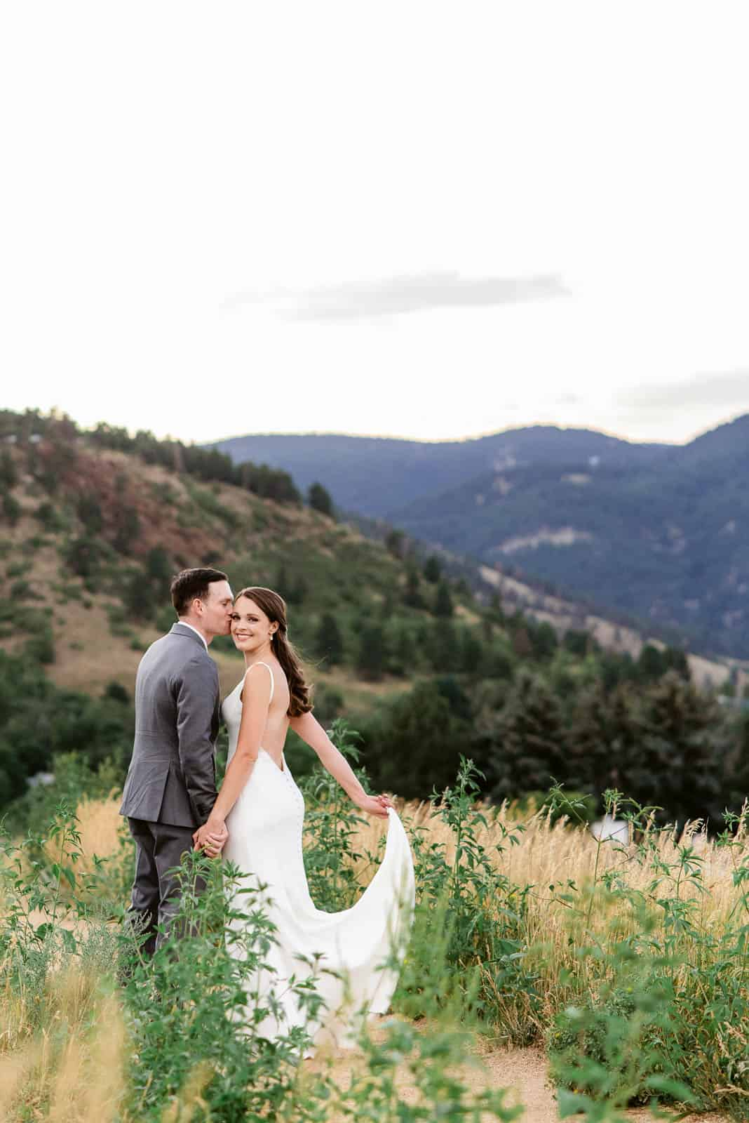 Groom kisses his bride as she looks back at the camera during their wedding photos at Chautauqua Park in Boulder, Colorado. Chautauqua Park is one of the best photo locations near Denver for engagement, elopements, and weddings.
