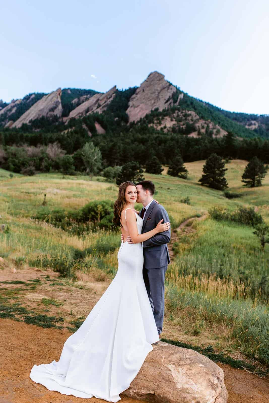 Couple poses in front of the Flatirons in Boulder, Colorado for their elopement photos. Chautauqua Park in Boulder is one of the best locations for photos near Denver