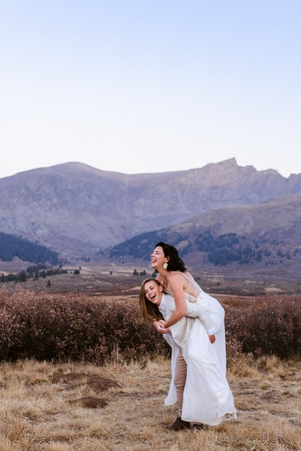 A gay couple laughs as they elope on a Colorado mountaintop. When deciding on an elopement vs wedding, they knew an elopement would fit their personality best. This photo shows them embracing and laughing together.