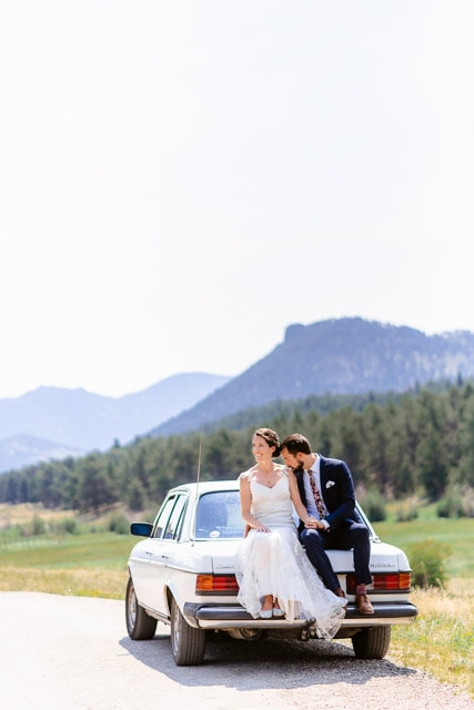 A couple sits on their car in Rocky Mountain National Park on their elopement day. Rocky Mountain National Park is one of the best locations near Denver to take photos for your engagement, elopement or wedding. The mountains create a spectacular landscape behind the couple in love.