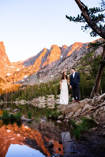A couple looks at each other during their elopement at Rocky Mountain National Park. The couple is at Dream Lake, a beautiful location for engagement, elopement or wedding photos near Denver.