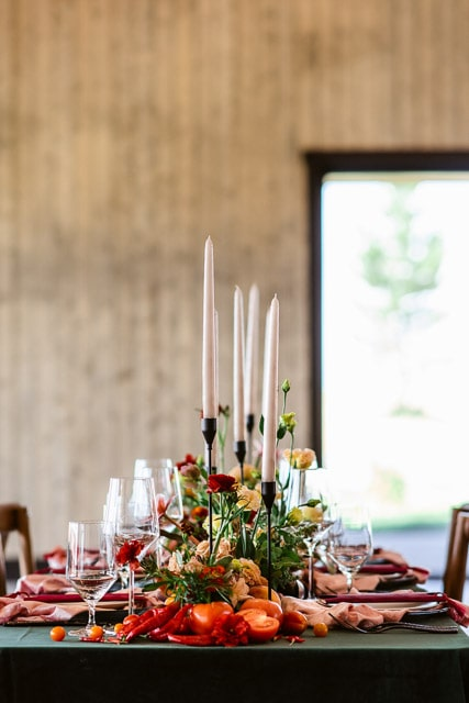 Lush table scape decor full of velvet, fresh fruits and vegetables with modern candlesticks. Bonnie Blues wedding venue hosts modern barn weddings in Colorado. Are you deciding between an elopement vs wedding? Don't forget the extravagant details that go into wedding planning!