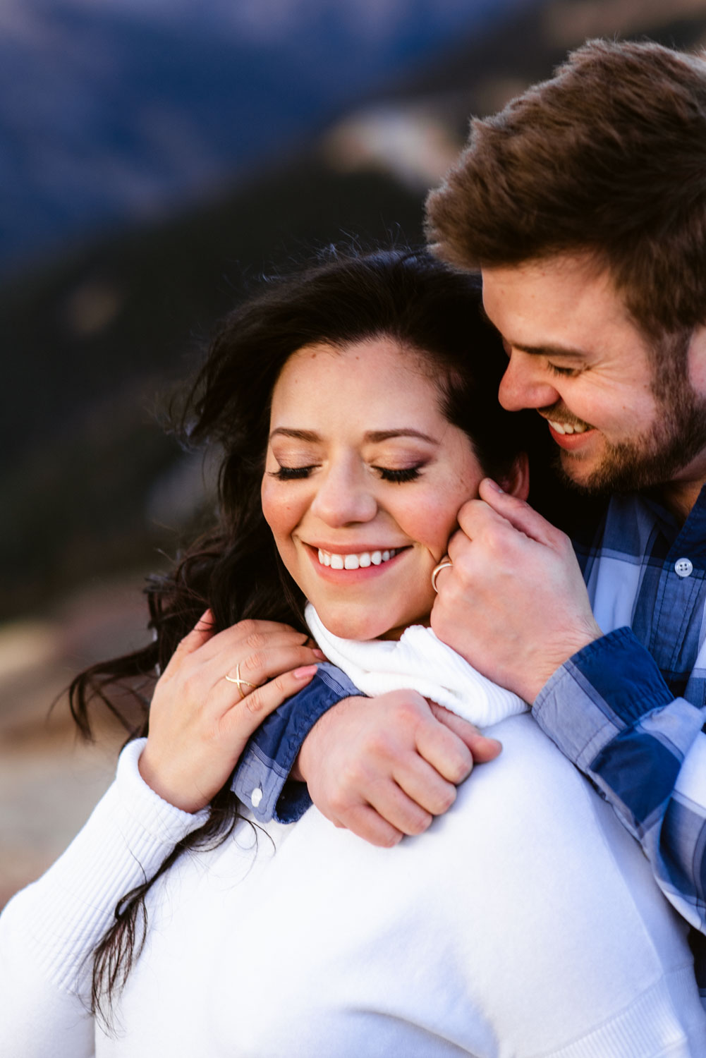 Couple smiles at one another while embracing on top of Colorado's Loveland Pass, a beautiful mountain pass with easy access from Denver. Loveland Pass is one of the best locations near Denver for engagement photos.