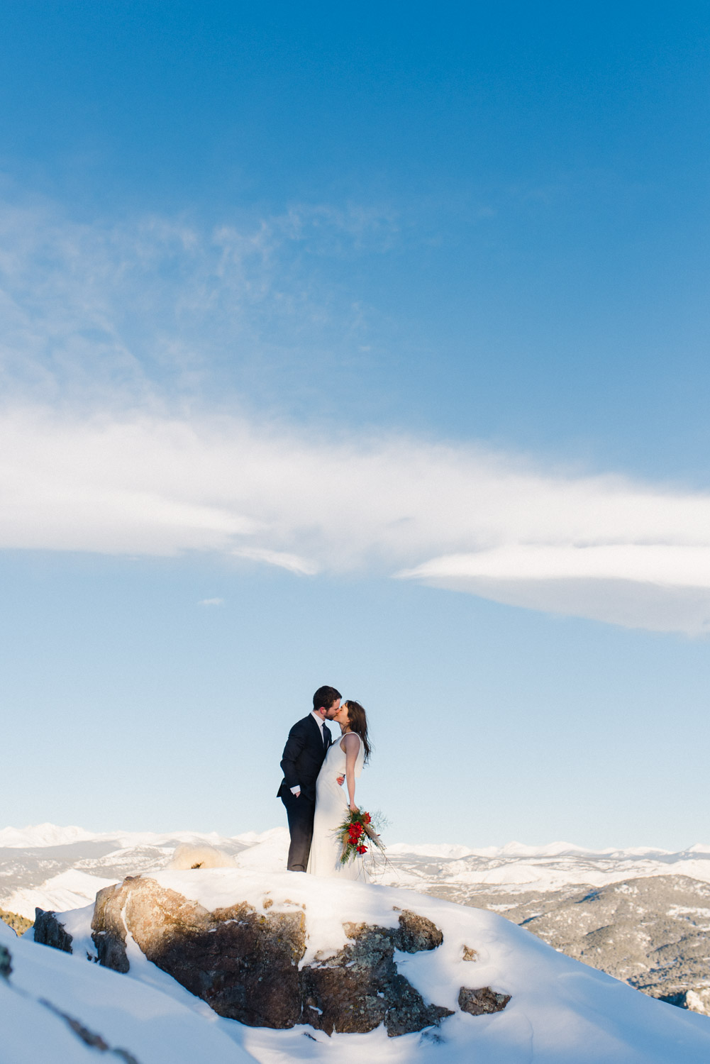 Couple kisses on top of the mountains at the Lost Gulch Lookout in Boulder, Colorado. Couple stands far away on the summit with wide blue skies behind them.