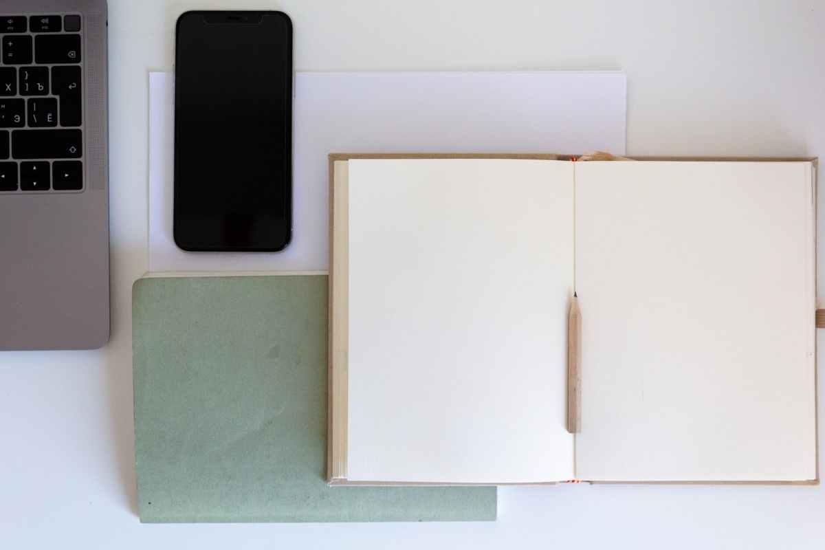 Bloco de notas aberto perto do teclado do notebook e do telefone celular na mesa branca. Fim da descrição.