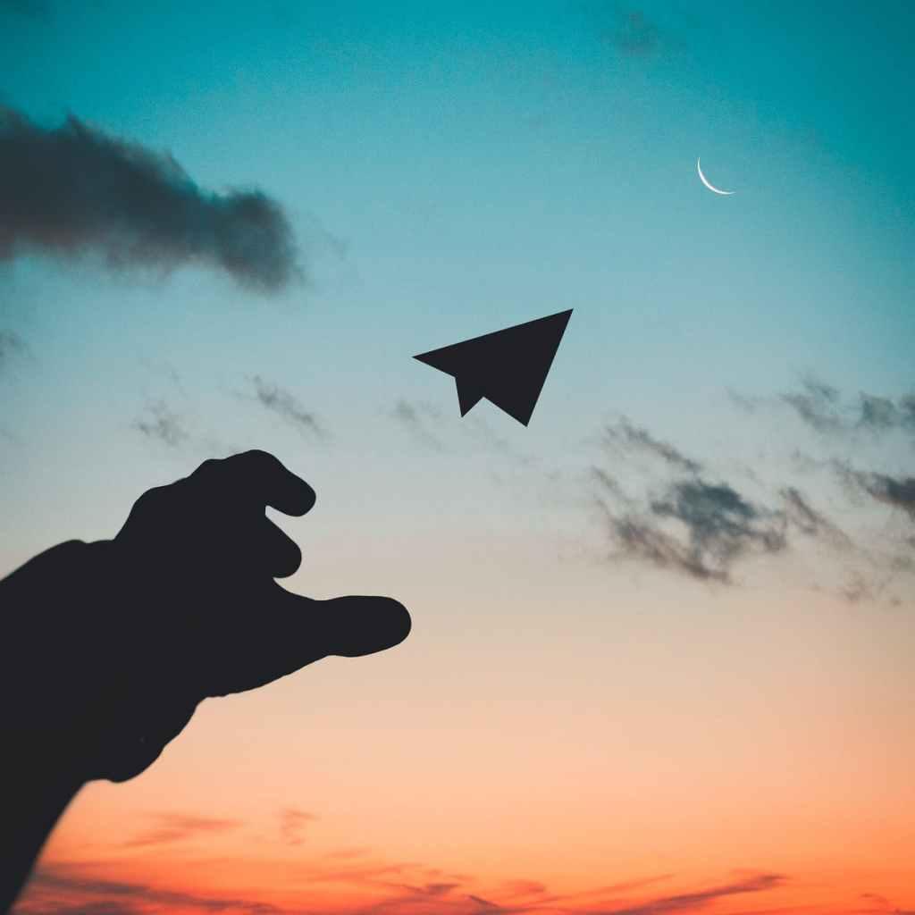 Um avião de papel num fim de tarde - como gosto desse horário! - representando um voo em sua fase 11 de 12. Fim da descrição.