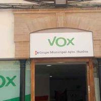 Trabajadora de una fundación de ayuda a los migrantes corona la sede de Vox con una bandera LGTBI