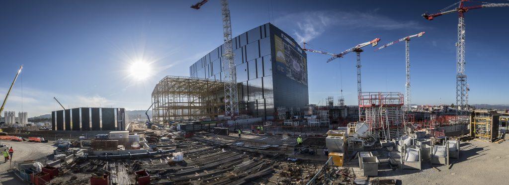 Les bâtiments de gauche à droite : usine à béton, bât des services, bât du chauffage radiofréquence ( la structure en acier pas terminée), hall d'assemblage (60 m. de haut) Devant le hall d'assemblage, les premiers niveaux du Complexe tokamak. Le cœur de la plateforme ITER (42 ha) est occupé par le Complexe Tokamak (7 niveaux dont 2 souterrains) dont les premiers niveaux commencent à émerger. Au centre de ce bâtiment de 440 000 tonnes, le Bâtiment Tokamak, qui abritera la machine. Côté nord, le Bâtiment Tritium, dans lequel sera géré et stocké le tritium (isotope de l'hydrogène qui constitue, avec le deutérium, le « combustible » d'ITER et des futurs réacteurs de fusion). Côté sud, le Bâtiment Diagnostics qui abrite tous les systèmes qui vont ausculter le plasma en temps réel. Quand le Complexe Tokamak aura atteint son 5e niveau, une structure métallique viendra prolonger le Hall d'Assemblage, de manière à ce que le pont roulant puisse positionner les pièces à assembler dans le « puits » du Tokamak. ©E.Raz/CCAS