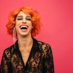 Portrait,Of,Drag,Queen,Laughing,On,Red,Background.,Gender,Fluid