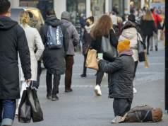 Düsseldorf, Nordrhein-Westfalen, Deutschland - Bettler sitzt in der Düsseldorfer Altstadt in Zeiten der Coronakrise beim zweiten Teil Lockdown zur Weihnachtszeit in der Fussgängerzone auf dem Pflaster, viele Passanten mit Einkaufstüten gehen vorüber. (Foto:Imago/Oberhäuser)