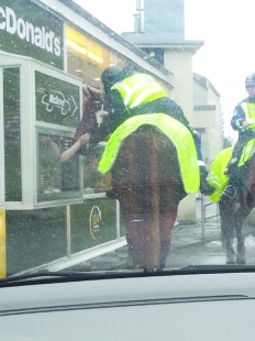 Police officer on horseback queuing at a McDonald's in Helsinki, Finland