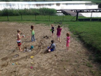 The children playing in the volleyball court/sandbox