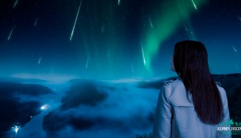 Woman stands staring at the comets from a high elevation