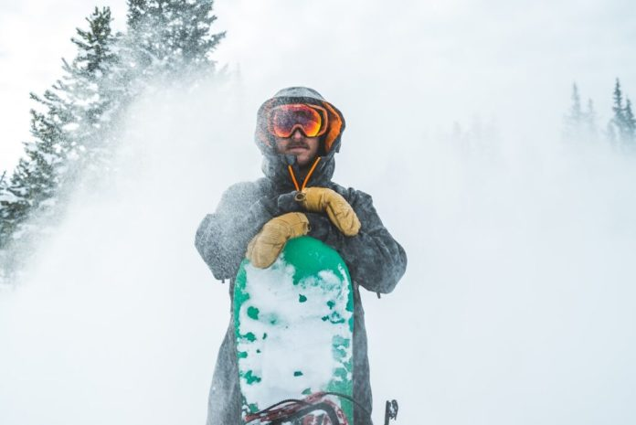 A snowboarder wearing bright goggles stands in front of the camera with his hands rested on his snowboard in front of him while a spray of snow is scattered all around him.