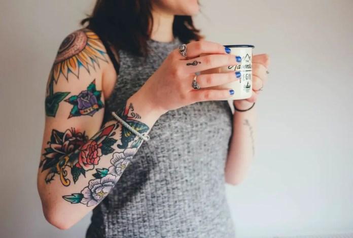Tattoo on arms of woman holding mug