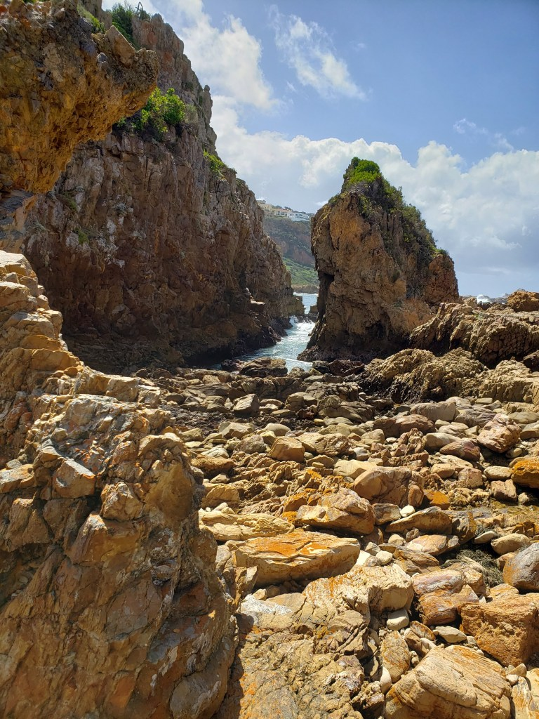rocky beach with mossy rock and lagoon in the background
