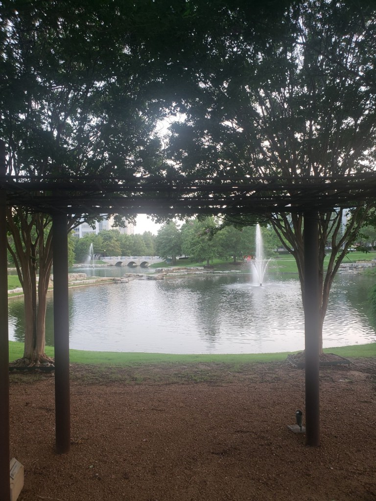 A steel arbor in the foreground with surrounding trees and lake with fountains