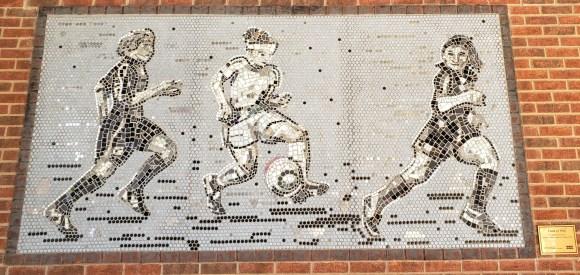 mosaic depicting girls playing soccer