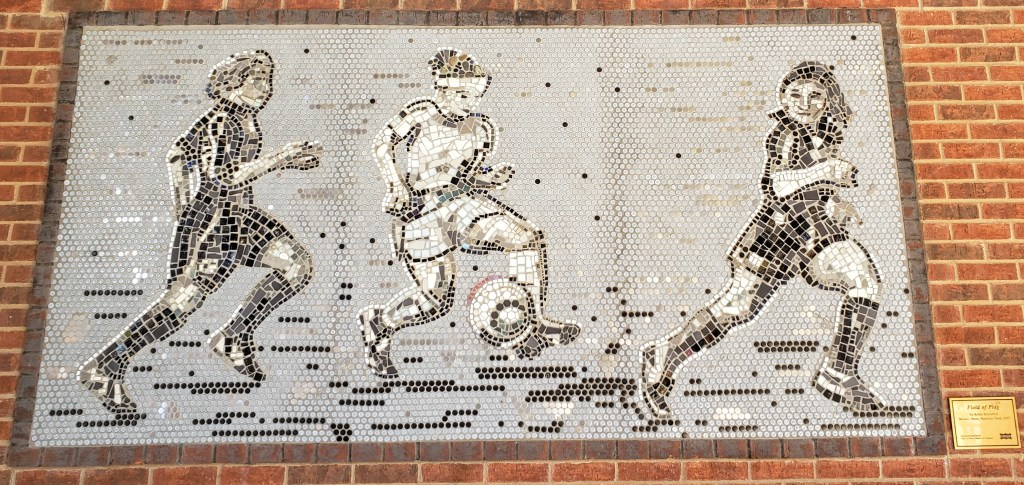 mosaic depicting girls playing soccer