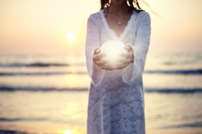 Close up moon in woman's hands sunset on the beach seaside background