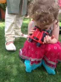 T using her binoculars to search for worms and lizards at the wedding ceremony (A's feet in background).