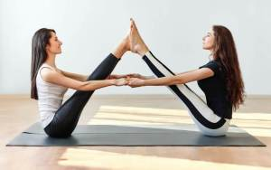 Partner Boat Pose: This pose takes some flexibility for both people. To modify, bend your legs and use a strap to connect your hands.