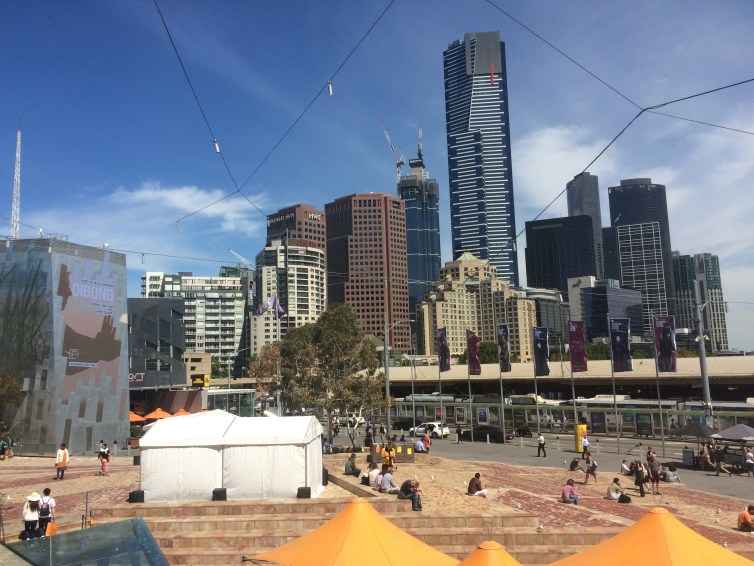 federation square, melbourne with skyscrapers in the background