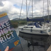 Wandering around Derwentwater Lake in the Lake District. The Marco Polo guidebook in front of the lake.