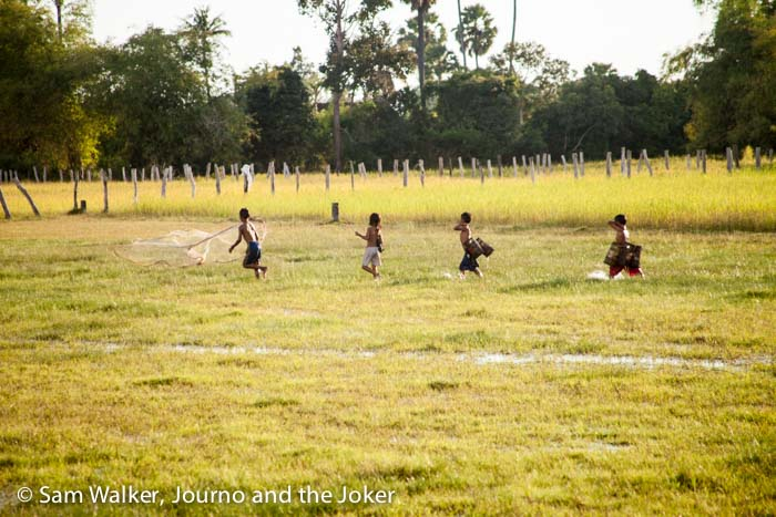Children throw net in wet field