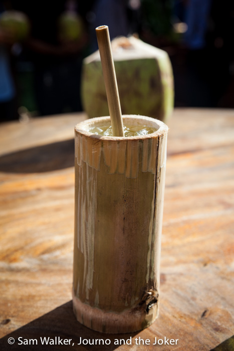 Drinking sugar cane juice with a bamboo cup and straw