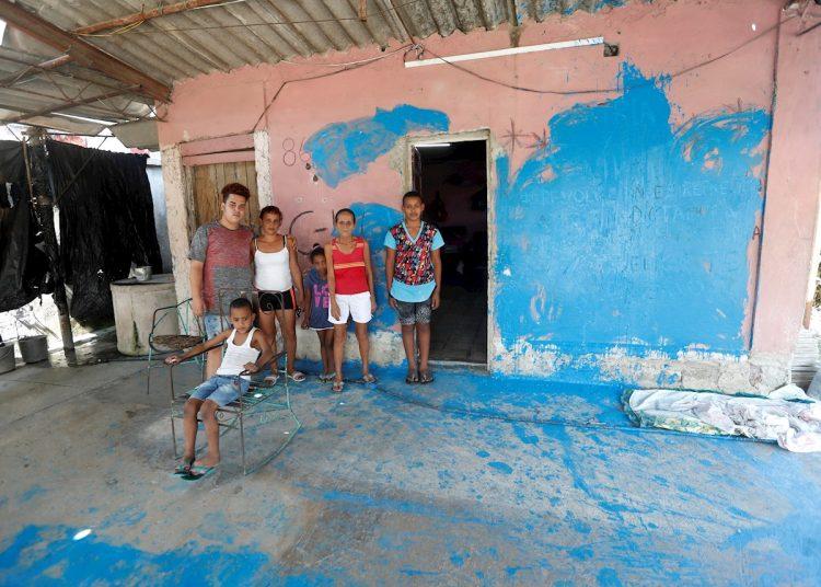 La activista disidente Anyell Valdés junto a su familia en el lugar que ocupa y que fue vandalizado durante un acto de repudio. Fachada azul. Foto: Yander Zamora/Efe