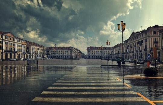 Pedestrian crossing and big plaza at city center under cloudy sky at rainy day in Cuneo, Italy.
