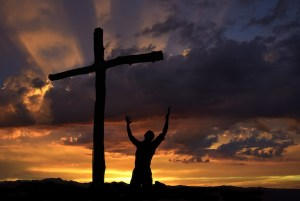 Dramatic sky scenery with a mountain cross and a worshiper (Creative Images)