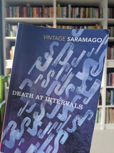 Cover of Death at intervals in front of a bookshel
