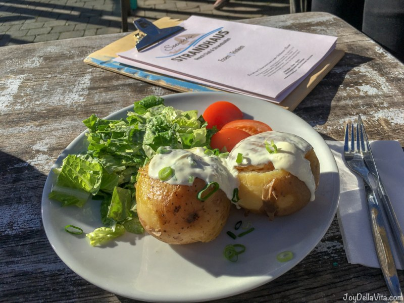 Stuffed baked potato with creme fraiche, gouda, spring onion and tomato, with a ceasar salad