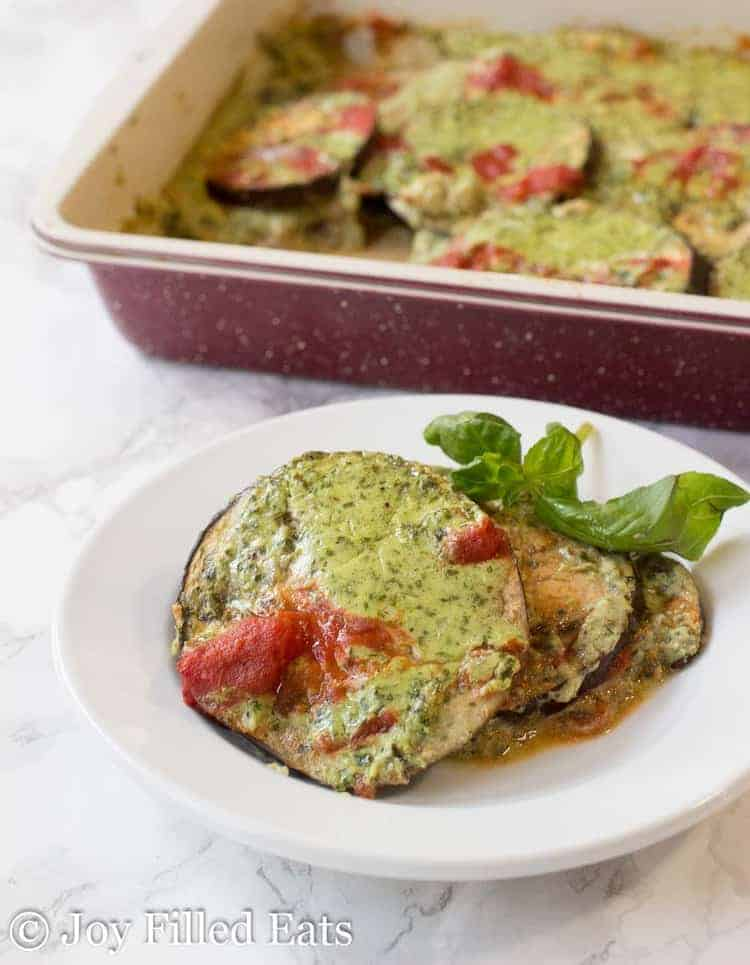 A piece of baked eggplant gratin on a white plate with the casserole in the background.