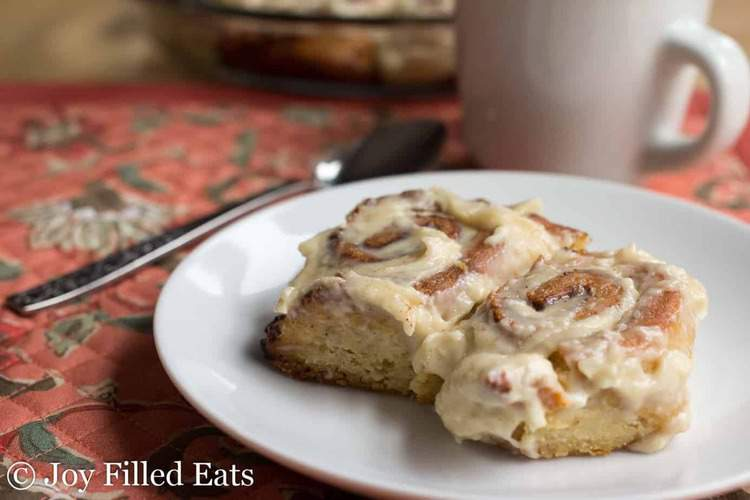Two cinnamon rolls on a white plate on top of a floral placemat