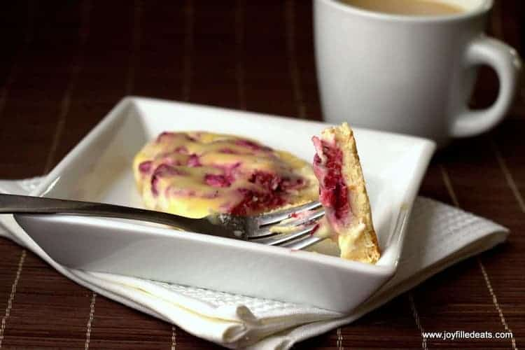 A pastry from the Raspberry Cream Cheese Danish Recipe cut into with a fork, a cup of coffee in the background