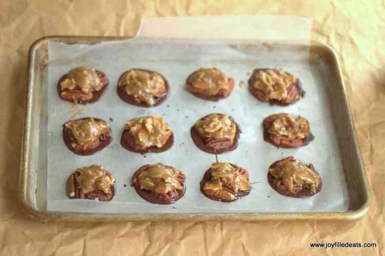 Toasted Coconut Toffee Pecan Turtles Candy being layered in a metal tray