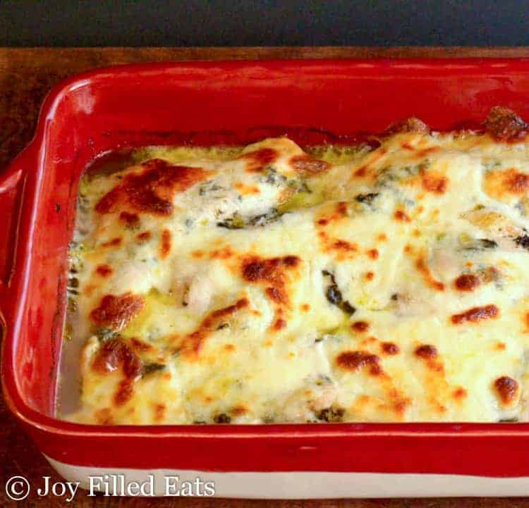 A red casserole dish of baked pesto chicken