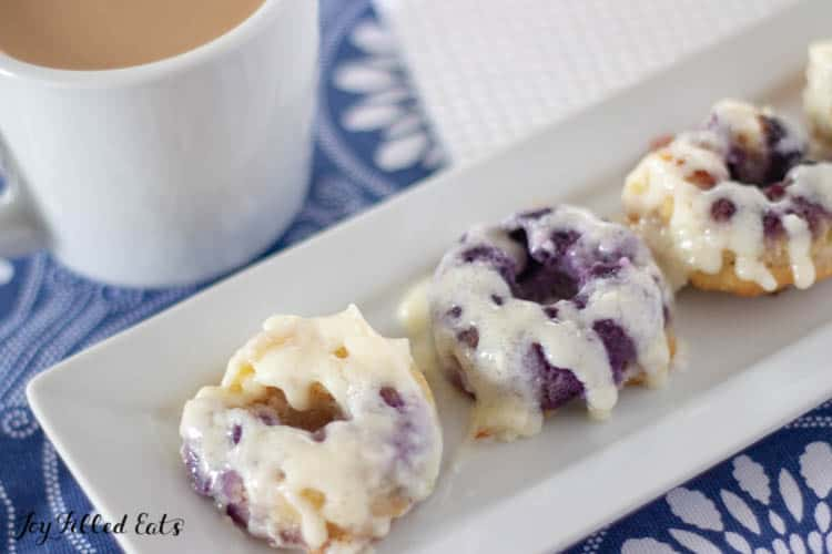 cream cheese glaze blueberry donuts on a rectangle white plate with a cup of coffee