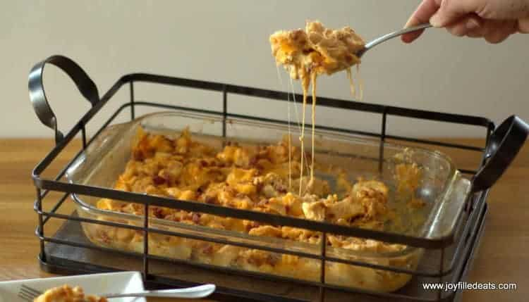 A casserole dish in an iron carrier with a hand lifting a scoop of Barbecue Chicken Bacon Casserole with cheese dripping down.