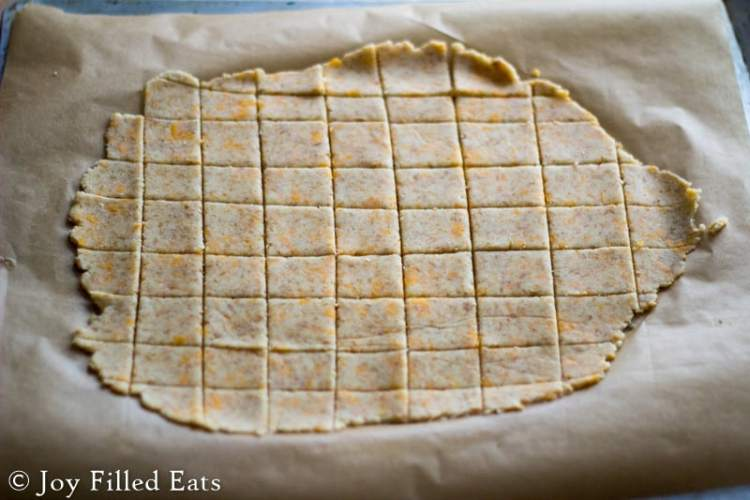 cheese crackers dough rolled out and cut into squares on parchment