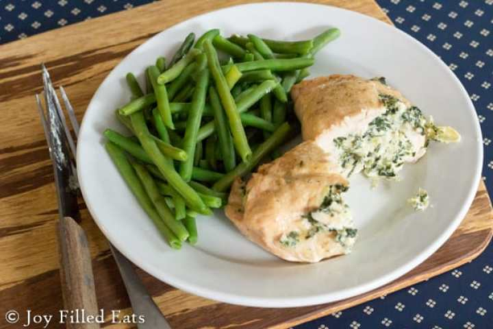 Spinach Stuffed Chicken Breast on a plate with green beans