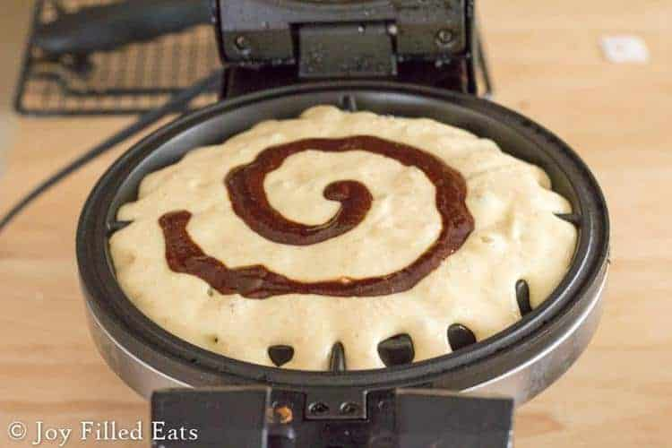 waffle batter on a waffle iron with a swirl of cinnmon on top