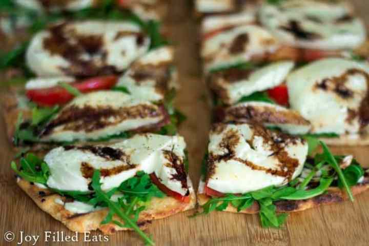 Low carb grilled pizza dough topped with a creamy herb sauce, baby arugula, tomatoes, fresh mozzarella, and a balsamic reduction.