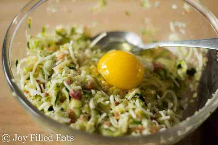 a glass bowl of raw shredded zucchini, cheese, and bacon with a raw egg on top